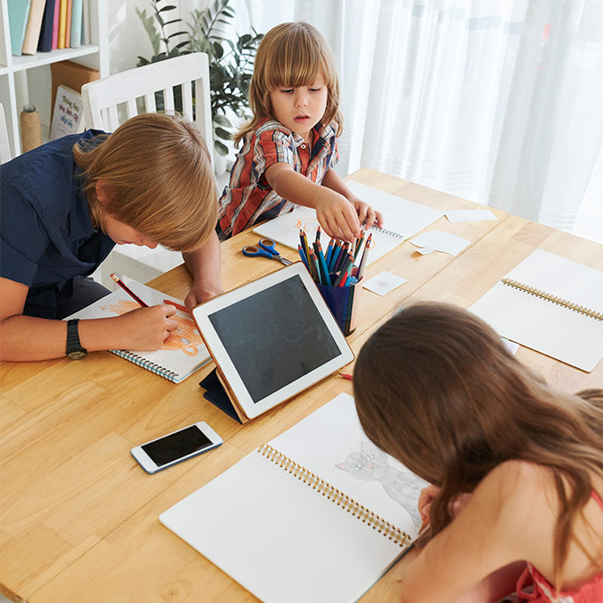Three children drawing at a large wooden homeschool desk in a sunny room.