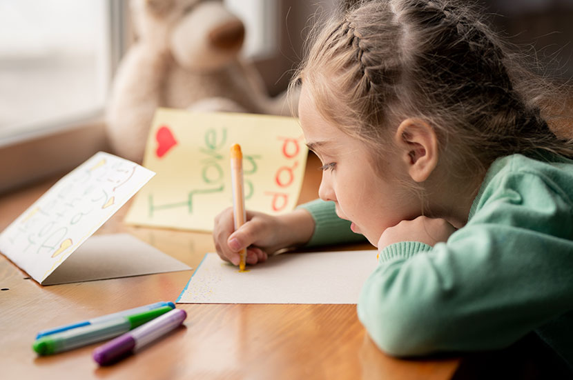 A little girl drawing cards at a small homeschool desk for her father.