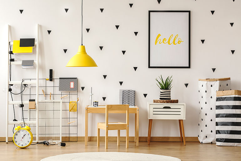 An airy minimalist room decorated in black and yellow, small homeschool desk against the wall.