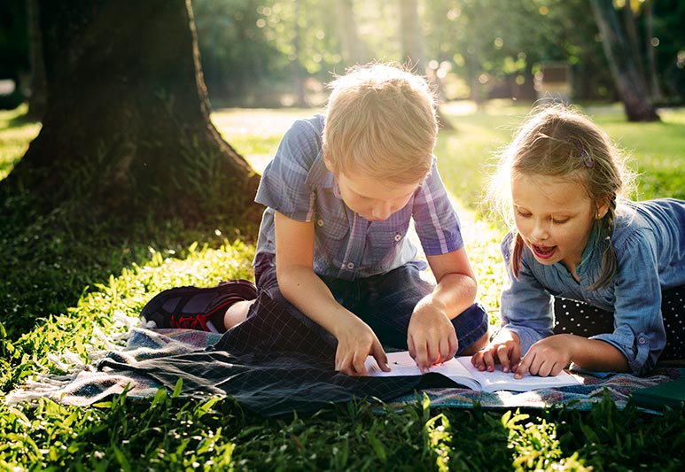 Two young children reading outside in the summer.