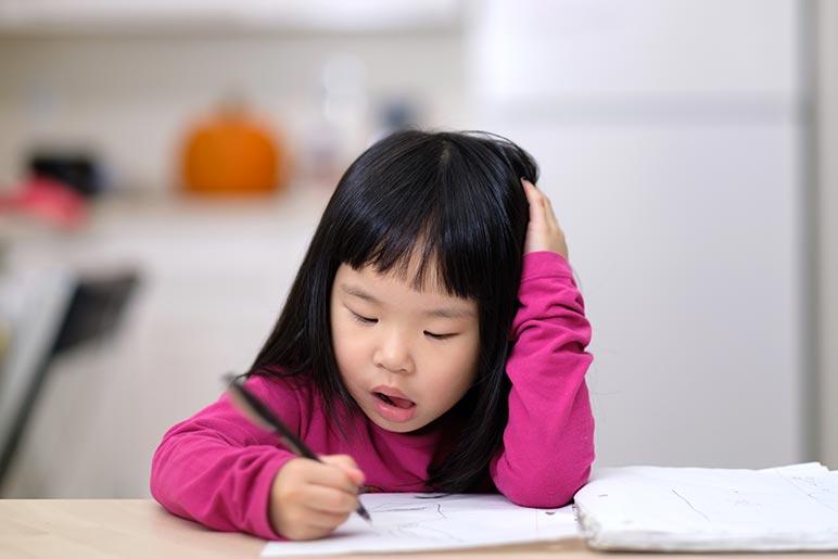 A little girl writing at a homeschool desk.