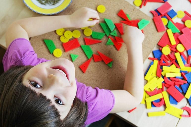 Best Maria Montessori quotes - a happy child in a Montessori classroom.