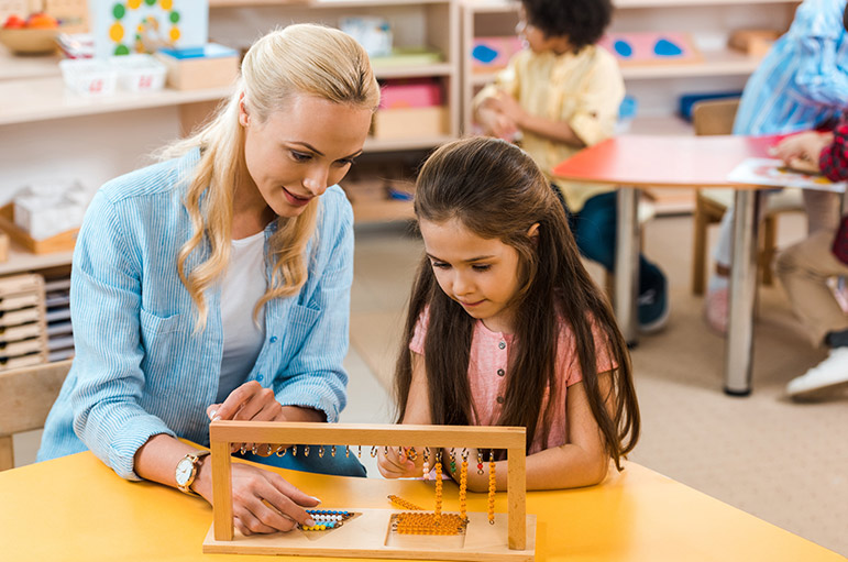 A teacher working with a child in a Montessori classroom.