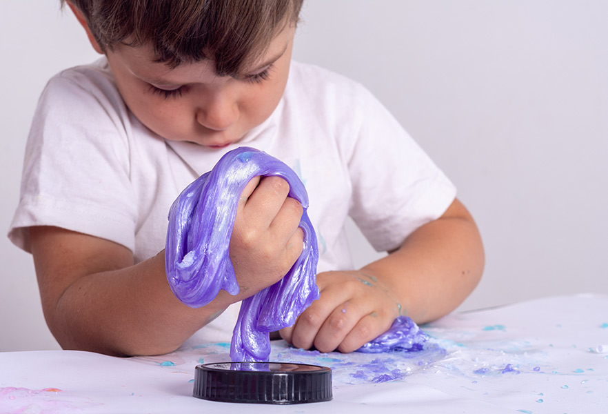 A little boy playing with Oobleck he made during a preschool homeschool science experiment