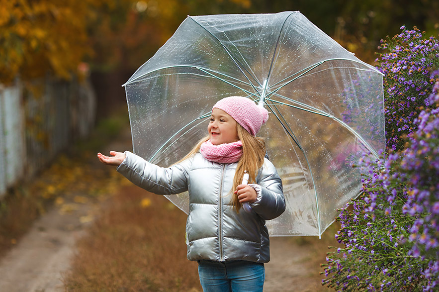 A preschool aged girl with an umbrella in early spring or fall.